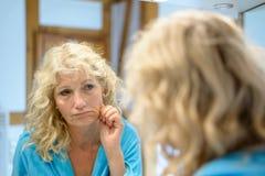 Ältere blonde Frau, die ihre Alternhaut überprüft Stockfoto