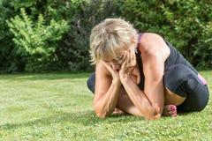 Ältere blonde Frau ist draußen entspannend Stockfotografie