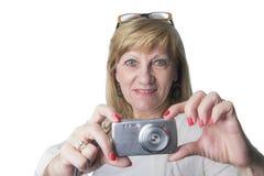 Ältere Blondine, die eine Digitalkamera halten Lizenzfreie Stockfotos