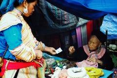 ältere Blume hmong Stamm-Mitgliedsfrau, die lokale Naturheilmittel und Medizin auf dem Dorflandwirtmarkt verkauft stockbilder