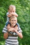 Ältere Bruderfahrt seine Junge auf Hals Lizenzfreie Stockfotografie