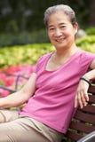 Ältere chinesische Frau, die auf Park-Bank sich entspannt Lizenzfreie Stockfotografie