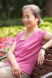 Ältere chinesische Frau, die auf Park-Bank sich entspannt Stockfotos