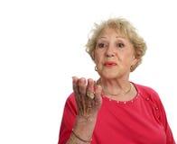 Ältere Dame Blows ein Kuss lizenzfreie stockfotografie