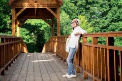 Ältere Dame, die auf der Brücke beim Warten auf Enkelkinder steht stockfotografie