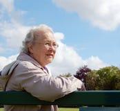 Ältere Dame, die auf Parkbank sitzt Stockfoto