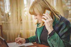 Ältere Dame, die Bestellungen, Arbeit vom Haus notiert Stockbild