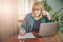 Ältere Dame, die Bestellungen, Arbeit vom Haus notiert Lizenzfreie Stockbilder
