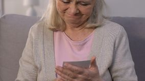 Ältere Dame, die betrachtet und Foto des geführten weg Ehemanns, gute Gedächtnisse umfasst stock video