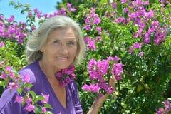 Ältere Dame, die draußen umfassend steht Lizenzfreie Stockfotos