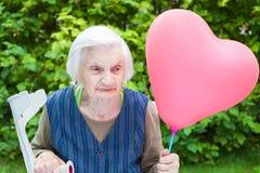 Ältere Dame, die einen geformten Ballon des Herzens hält Lizenzfreies Stockfoto
