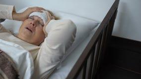 Ältere Dame, die im Bett mit Stirnkompresse und leidenden schrecklichen Kopfschmerzen liegt stock video