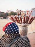 Ältere Dame, die kandierte Frucht auf einem Stock auf einem Strand verkauft stockfotos