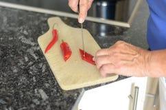 Ältere Dame, die Pfeffer des roten Paprikas schneidet Stockfotografie