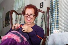 Ältere Dame, die Sie beim Stricken betrachtet Lizenzfreies Stockbild