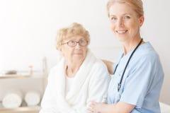 Ältere Dame im Haus mit Krankenschwester lizenzfreies stockbild