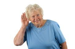 Ältere Dame mit der Hand an ihrem Ohr stockfoto