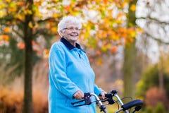 Ältere Dame mit einem Wanderer im Herbstpark Stockfotografie