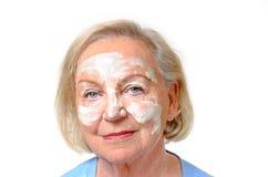 Ältere Dame mit kosmetischer Creme auf ihrem Gesicht Lizenzfreie Stockfotos