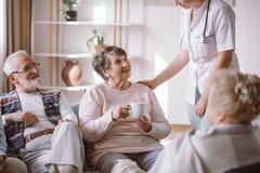 Ältere Dame mit Krankenschwester und Sitzen mit ihren älteren Freunden stockfotografie