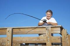 Ältere Dame Reels in den Fischen stockbild