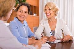 Ältere Damen, die Dokumente unterzeichnen stockbilder
