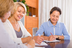 Ältere Damen, die Dokumente unterzeichnen stockbild