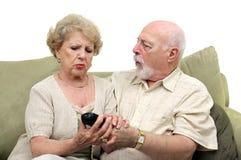 Ältere, die über Fernsehapparat Remot kämpfen Stockfoto