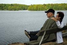 Ältere, die auf einer Bank stillstehen Stockfotos