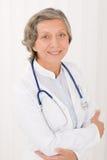 Ältere Doktorfrau mit dem Stethoskoplächeln lizenzfreies stockfoto