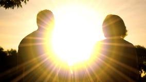 Ältere Ehemann- und Frauschatten in der Sonnenuntergangbeleuchtung, Entspannungspark zusammen stockbild