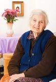 Ältere einsame Frau sitzt auf dem Bett Stockbild