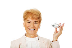 Ältere elegante Frau des Lächelns, die eine Spielzeugfläche hält Stockfotos