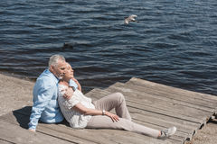 Ältere entspannende Paare beim Sitzen auf Pflasterung am Flussufer Stockbild