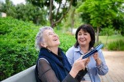 Ältere erwachsene Frau und ein Betreuerlachen, das eine Tablette in ihren Händen beim Sitzen auf einer Parkbank hält lizenzfreie stockfotografie