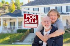 Ältere erwachsene Paare vor Real Estate-Zeichen, Haus Stockfotos