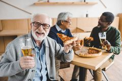 Ältere Fleisch fressende Pizza mit Bier stockbilder