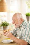Ältere Fleisch fressende Pizzascheibe zu Hause Stockfotos