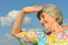 Ältere Frau auf dem Hintergrund des Himmels Stockfoto