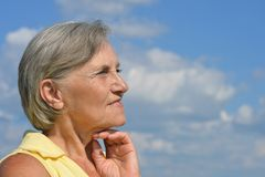 Ältere Frau auf dem Hintergrund des Himmels Stockbilder
