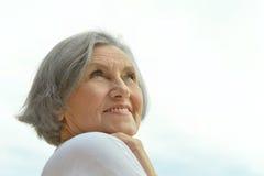 Ältere Frau auf dem Hintergrund des Himmels Lizenzfreies Stockfoto