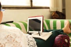 Ältere Frau auf der Couch mit Laptop stockfotos