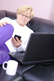Ältere Frau auf der Couch am Telefon. Stockbild