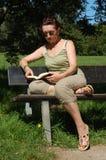 Ältere Frau auf einer Parkbank Stockfotografie