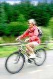 Ältere Frau auf Fahrrad Stockbild