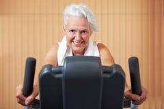 Ältere Frau auf Fahrrad in der Gymnastik stockfotos