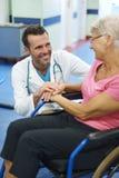 Ältere Frau auf Rollstuhl zujubelnd durch Doktor Stockbilder