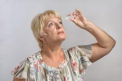 Ältere Frau behandelt ihre Augen mit Medikation Stockbilder