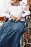 Ältere Frau beim Rollstuhlerhalten lizenzfreie stockfotos