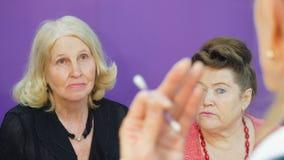 Ältere Frau berät sich mit Kosmetiker über Hautpflege Gruppenberatung des cosmetologists stock video footage
